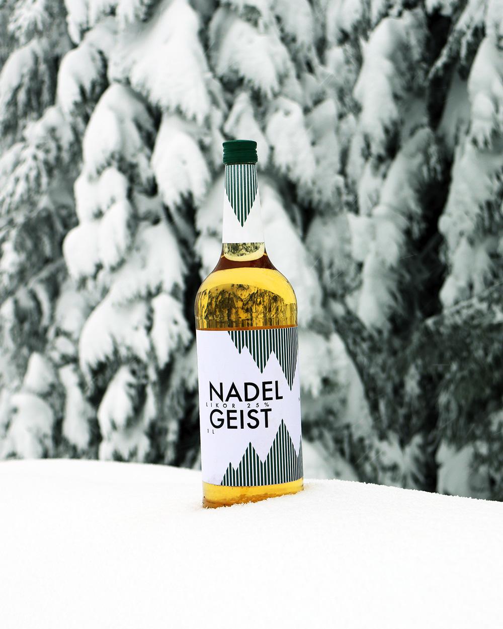 Eine Nadelgeist Likörflasche steht im Schnee vor Nadelbäumen